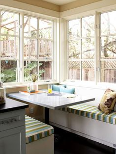 A cozy kitchen banquet with cute striped cushions.
