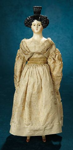 German Paper Mache Lady Doll with Rare Beehive Coiffure, circa 1830, wearing a silk gown and undergarments.