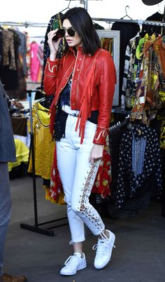 Kendall Jenner took her street style game to the next level with white lace-up pants and a fringe red leather jacket.