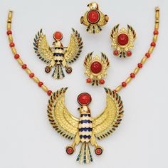 Coral, Enamel and 18K Gold Suite (4)   Including a necklace suspending a phoenix eagle with blue and white enamel body, and plique-a-jour enamel feathers, further decorated with three coral 'shen' symbols;, length 19 1/4 ins; together with similarly designed brooch, ear clips and ring