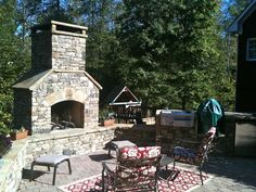 Outdoor Stacked Stone Fireplace with Seating Walls attached to Outdoor Kitchen