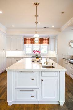 The brass fixtures & the orange striped blind (& wood floors) add a nice little bit of color to a white kitchen.
