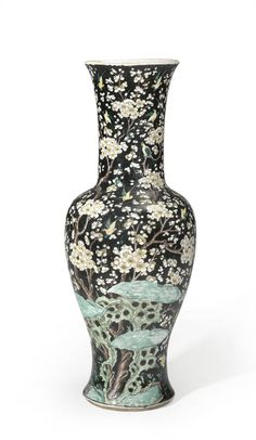 A large famille noire enameled porcelain vase  Chenghua mark, 19th century  Thickly potted with a flared rim to the long trumpet neck and body of inverted pear shape flaring outward above a set-in foot ring, painted in the characteristic enamels with birds alighting on densely flowering prunus branches above garden rocks, peony and bamboo plants, the recessed base covered with a colorless glaze and bearing the six-character mark in underglaze blue inscribed within a double ring.