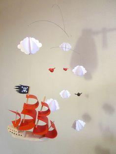Mobile le bateau volant des pirates, grand modèle en fimo, papier et balsa Ce mobile pour bébé est composé d'un bateau de pirate à voiles rouges, de 3 petits oiseaux rouges et noirs en pâte fimo...