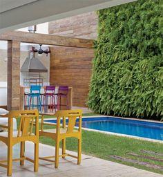 Ocupada em grande parte pela piscina, a área externa ganhou este jardim vertical de 10,30 x 4.20 m (Folha Paisagismo). Presas a módulos metálicos, 860 mudas de aspargo-pendente, renda-portuguesa e samambaia-paulista produzem um enfeite em camadas