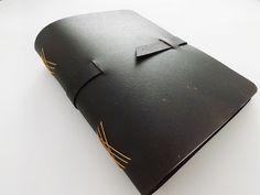 Agenda/caderno de anotações estilo journal com 100 folhas (200 páginas), capa flex em recouro cor preta, costura romancesca em fio encerado, folhas em sulfite branco premium sem pauta e fechamento por alça de recouro. <br> <br>Ótima e charmosa opção de presente! Já vai embalado. <br> <br>Pode ser feita com o primeiro nome ou iniciais da pessoa bordado na capa. <br> <br>Disponível também nas cores: <br>- roxo <br>- azul escuro <br>- rosa <br>- natural <br>- preto <br> <br>Para personalização…