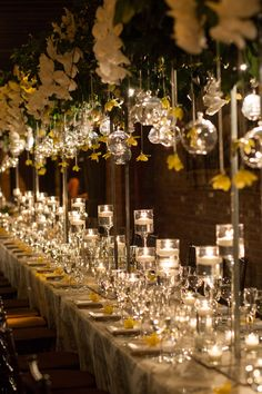 Orchids & Orbs Above Guest Tables  Photography: Josephine Photography Read More: http://www.insideweddings.com/weddings/traditional-jewish-ceremony-romantic-yellow-reception-in-nyc/1036/