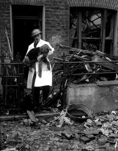 World War II, 25th October, 1940. A white coated and steel helmeted P.D.S.A. man taking a dog from a wrecked house in the East End of London, after an air raid. Note the cat sitting on the debris. (Photo by Popperfoto/Getty Images)