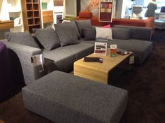 Dark gray L-shaped couch with lots of pillows, matching ottoman.