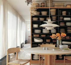 The open shelves in Grethe Meyer's dining room are filled with decades worth of ceramics of her own design. The Shaker table and chairs are ...