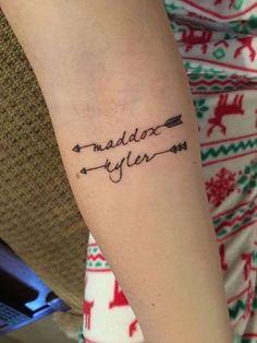 Tatuaje con nombre con flechas - Diseño de tatuaje con dos nombres en el interior del brazo, en color negro con diseño original de flechas. Este tipo de tatuajes son tendencia.