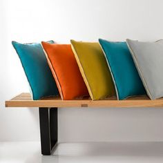 Natasha Marshall - Alibi Woven Fabric Collection - A simple wood and black metal bench with 5 plain square scatter cushions in aqua blue, orange, green-gold and light grey Small Cushions, Floral Cushions, Bolster Cushions, Embroidered Cushions, Decorative Cushions, Scatter Cushions, Outdoor Cushions, Pillows, Contemporary Cushions