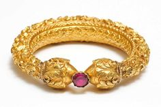 Gold Repousse Bangle Tamil Nadu India 19th Century,Diameter: 10cm. A sheet of pure gold is worked over a lac core in floral motifs terminating in two onion head finials between which is held a glass foiled stone.