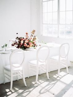 clean modern white reception table scape with a pop of jeweled berry tone florals