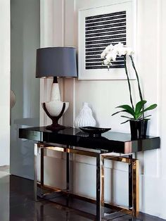 Interior design: rose gold and gloss black console hall table. White orchid in pot, table lamp, ceramic vase and black and white art print