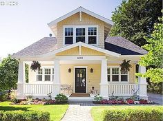 pale yellow/cream body, white trim and white painted porches, dark front door