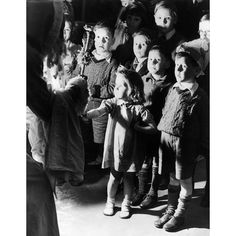 30th December 1941:  At Aldwych station, London Father Christmas hands down presents from the tree to children who regularily sheltered there with their families during WW II