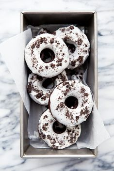 oreo donuts topped with crushed oreos in baking panSometimes, there's nothing better than an Oreo. Well, except for when you take a bunch of Oreos, crush them up, and put them inside chocolate donuts. And then top those donuts with a thick vanilla frosting and more crushed Oreos.