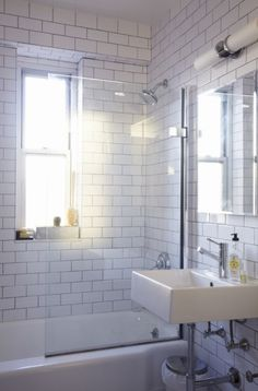 The original bathroom was a crumbling mess of Pepto Bismol pink and black tile. The only original detail I saved was the bathtub which was reglazed, and I was amazed with the results.  I wanted the space to be modern, clean and classic and used a combination of subway tiles and penny tiles with light grey grout. Recessing the medicine cabinet into the wall, installing a tankless toilet and floating sink, gave the small space an airy feel.