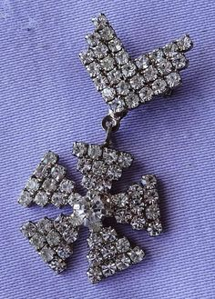 This fabulous Art Deco piece consists of a chevron shaped brooch with a star shaped pendant hanging beneath. Made from base metal with a silvertone finish, it is adorned with tiny shimmering diamante stones.