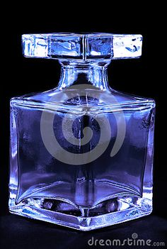 A glass bottle with a glass stopper on a black background