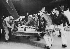 "An injured crewman being removed from his US 8th Air Force B-17 bomber. In ""A Memory Between Us,"" Maj. Jack Novak is wounded by flak on his first mission from England."