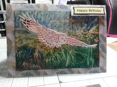 "Made by Teresa Penfold - This card has been made with Tattered Lace Barn Owl, the mat is paper from one of the Tattered Lace Magazines, and the background is created with Encaustic Wax. The waste from the Barn Owl was scanned in on the Brother Scan N Cut to form the ""mat"" behind the owl."