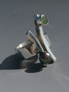 sterling silver ring with a large black pearl and peridot set stone by craig moore