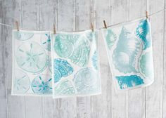 "Seashell Kitchen Towel. Each towel has it's own beach phrase. ""The Voice of the Sea Speaks to Me"" - Sand Dollar. ""Seashells are love letters in the sand"" -Spiral Shell. ""May you always have a shell in your pocket and sand in your shoes"" -Conch."