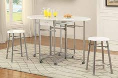 3 Pc Dining Table & Chair Set CS100080 Description : This three piece counter height dining set is the perfect addition to a smaller sized dining or bar area. The table has two 17 inch leaves extending the length of the table from 15.75 to 51 inches. A small drawer underneath the table top adds convenient storage for napkins or other smaller items. For easy movement the table has casters, perfect to stow away when not in use. The table and the matching stools are finished in white with a…
