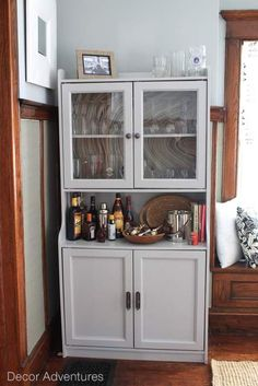 A wood colored cabinet gets a makeover with paint and is re purposed into a bar. Yes you can paint laminate furniture.
