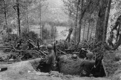 Battle of Hurtgen Forest - Two GI's inspect a German machine gun position. Around the tunneled outpost are 2 MG42's, field radio and telephone, rifles, helmets, ammunition, and multiple grenades.
