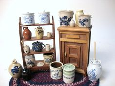 """Two crocks with lids & butter churn by Vernon, open crock & chamber pot by Jane Graber, 2 crocks, cooler, bird feeder, bank, redware jug, cups by CNC (Carolyn Curran), batter jug by Phyllis Howard, Mullica Hill crock by Lytle, rug by Betty Krueger, other pottery pieces unidentified unmarked shelf, icebox by Shackman, 4 3/4"""""""