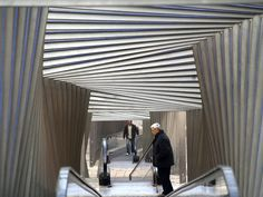 a twisting sectional structural framework shelters a moving walkway transporting people through the town while providing a protected dynamic interior.