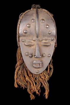 Africa | Face mask from the Bete people from the Ivory Coast | ca. 19th to early 20th century | Wood, brass nails, iron and fiber | Note this is a relatively small mask only measuring about 17.5 cms in length.