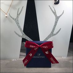 The ribbon repeats the brand identity while the Swarovski Gift Box Reindeer Antlers say Christmas. And while the Swarovski Gift will most certainly. Swarovski Gifts, Reindeer Antlers, Visual Merchandising, Hanukkah, Gift Wrapping, Box, Christmas, Gift Wrapping Paper, Xmas