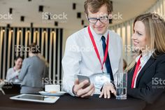 Businesswoman looking at colleague using smart phone royalty-free stock photo