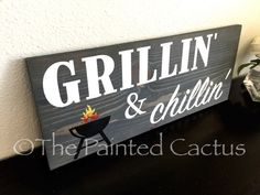 This outdoor kitchen sign features a charcoal gray stain with white lettering and a multi-colored grill. This wood sign would make the perfect Father's Day gift or for the grill master of your family.
