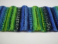 This is a simple scarf that is easy and fun to knit. It has a subtle wave and features rows of eyelets for added interest. It is made up of an eleven row pattern, eight of which are plain knit rows.