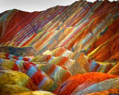 Believe it or not, this technicolor range actually exists.  The mountains are part of the Zhangye Danxia Landform Geological Park in China. Layers of different colored sandstone and minerals were pressed together over 24 million years and then buckled up by tectonic plates.