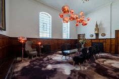 The vestry at the Church has a large Tom Dixon melt chandelier installed. The Wingback dinning chairs surround two large glass topped Pylon tables sit on the Smoke Tom Dixon X ege™ carpet. The Wingback sits in the corner with a floor Melt light a Pylon side table and a Melt table lamp.