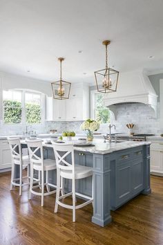 White Kitchen with Stacked Cabinets and Grey Island. Gray marble backsplash and brass gold pendant lights. Love the white bar stools.