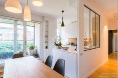 Cuisine semi-ouverte avec verrière pour un ambiance lumineuse. Une rénovation réalisée par Sophie Laurière.