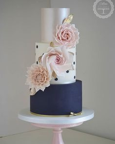 wedding cake with navy blue bottom tier, pearl top tier, and blush details