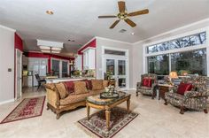 This lovely den with travertine floors is open to the kitchen has French doors leading out to the covered patio and grounds, and has a terrific pool view.