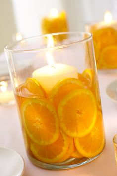 So Pretty!  To make these candle arrangements, start with varying size glass cylinder vases. Place a pillar candle in the center. Fill the remaining area in the vase with orange slices and add water. Leave at least the top quarter of the pillar candle exposed for burning.