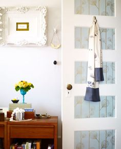 Looking for quick cottage style? Update small items in your home for a casual, eclectic feel. In this bedroom, a paneled door is brought back to life with the addition of eye-catching wallpaper and an ornate white frame pops on the wall.