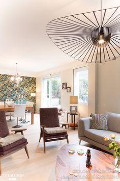 Salon lumineux et harmonieux avec sa suspension Vertigo, ses fauteuils à la découpe vintage