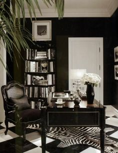 Black and white, love the zebra rug on the checkered floor, the all-black chair and the tall black vase with flowers.  The white door seems to disappear, interesting.  #offices_and_studios