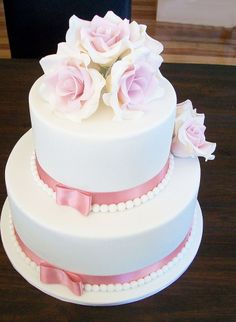 A two tiered cake embellished with vintage roses, satin ribbon and ivory beads.